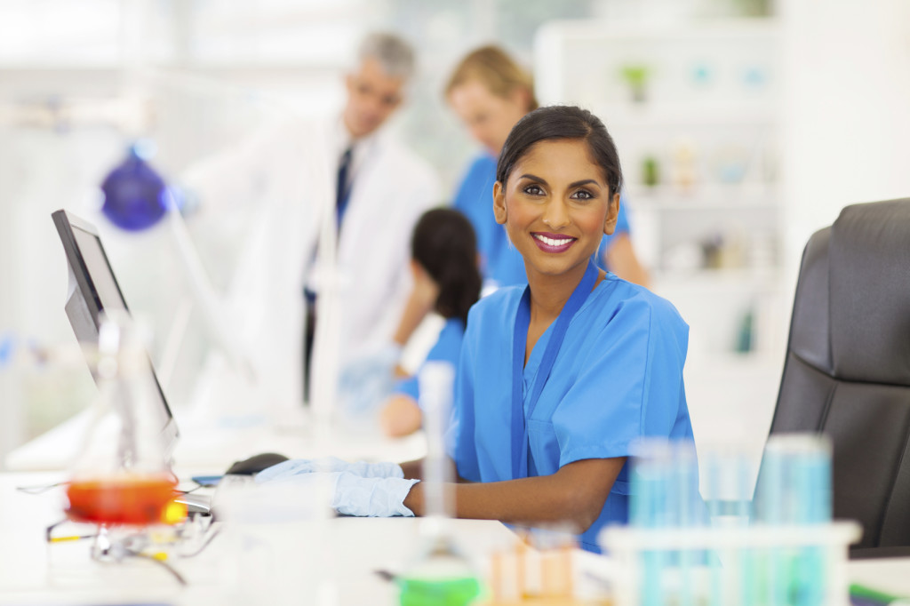 cheerful indian laboratory worker using computer in lab